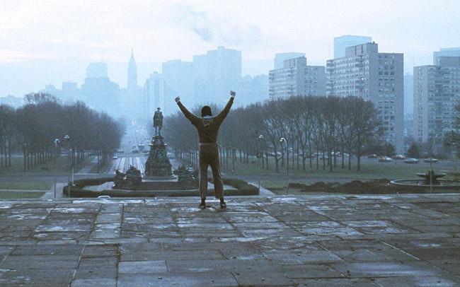 Sylvester Stallone lève les bras au ciel dans Rocky
